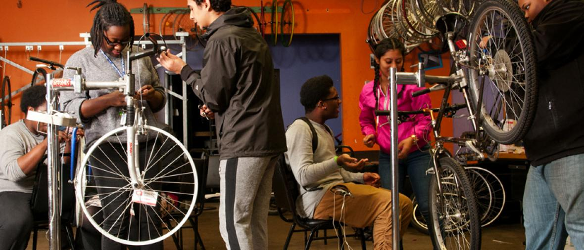 a group of youth fix bikes