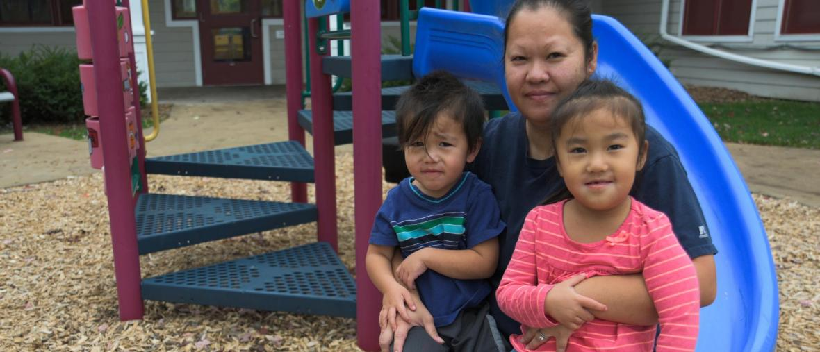 a woman holds her two children on a playground