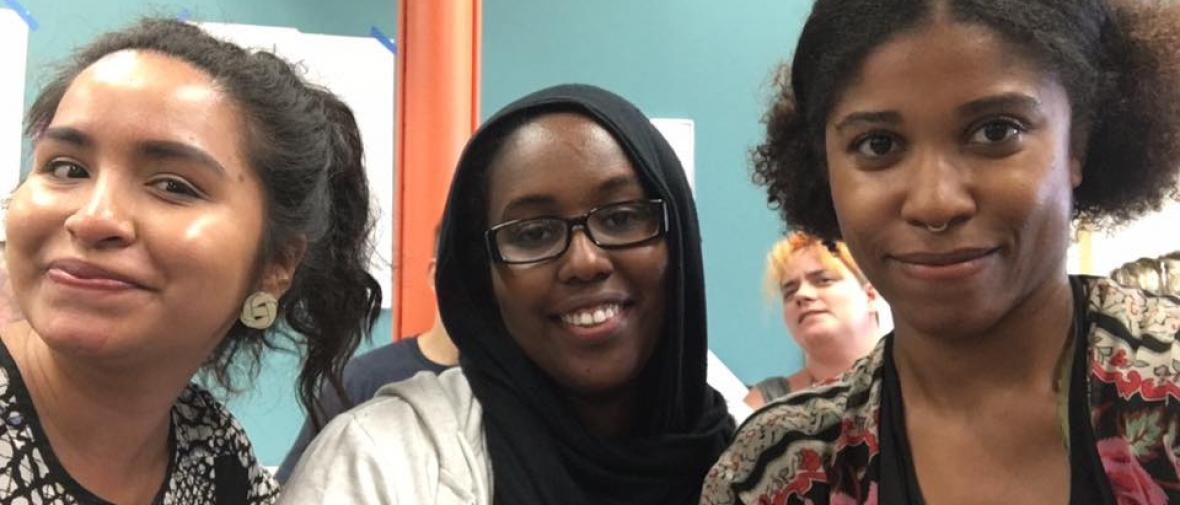 Three women of color smile at the camera