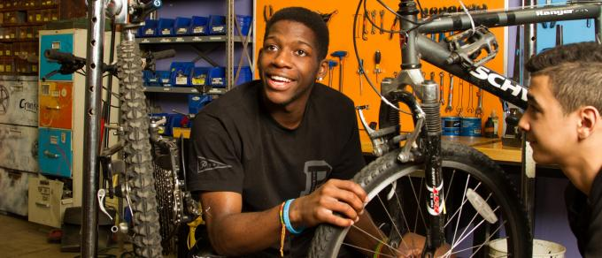 An african american young man smiles while fixing a bike
