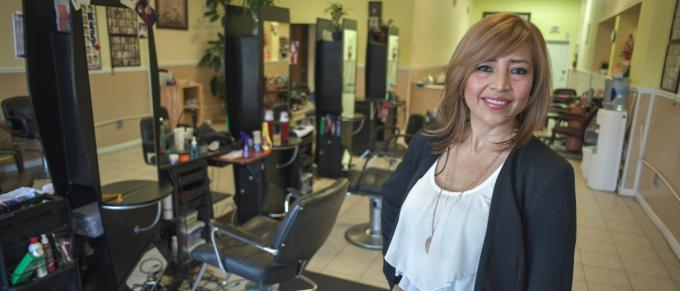 Woman standing in a beauty salon next to a chair