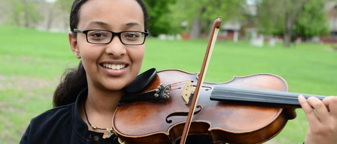 a young african american woman plays the violin